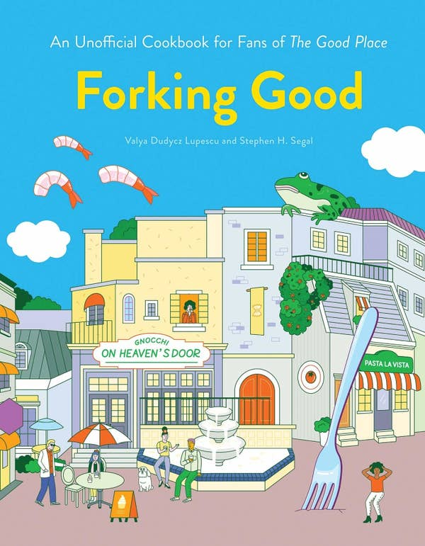 The book cover of a Good Place cookbook which is a cartoon-like drawing of the town square