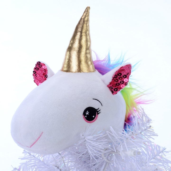 A close-up of the unicorn head topper with a gold horn and a rainbow mane