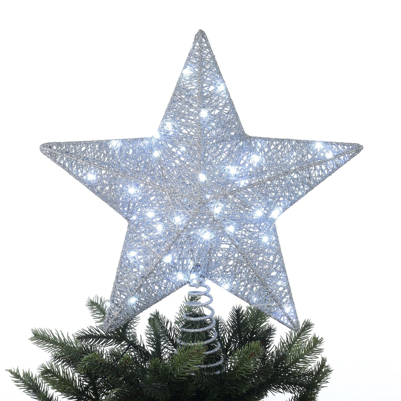 The star with its lights on, on top of a Christmas tree