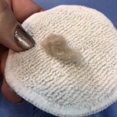 reviewer photo of peach fuzz on white cotton round