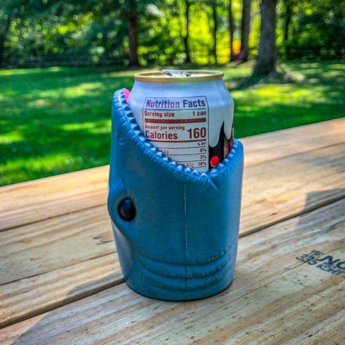 Shark mouth-shaped can holder with soda can inside of it on a picnic table