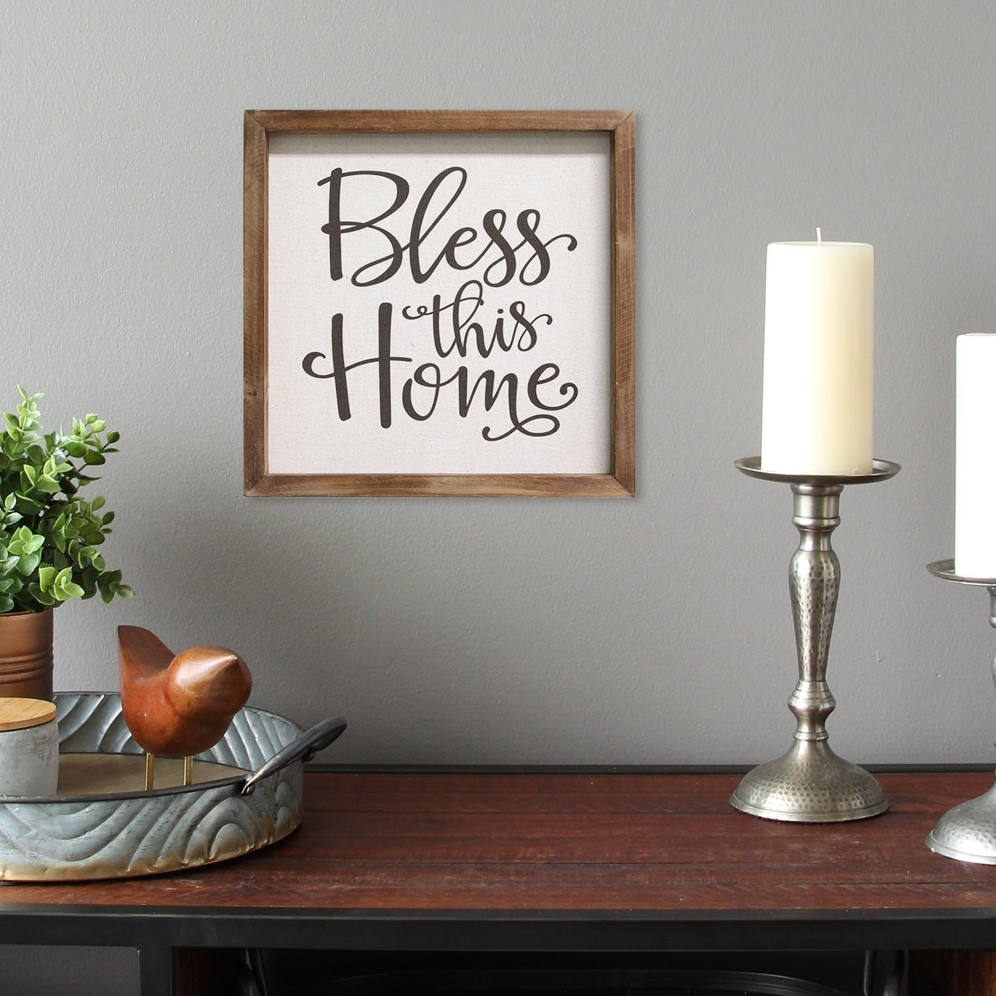The sign in a wood frame hanging on a wall above an entryway table