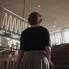 The back of Beth as she walks up a flight of stairs; she is wearing a houndstooth dress with a black cover-up on top