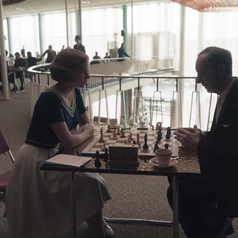 Beth playing a chess game against an opponent; she is wearing a short-sleeved, navy blue shirt that has stripes running across the neckline, a white skirt and white shoes
