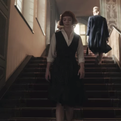 Beth walking down some stairs; she is wearing a mid-length plaid dress with a white collared shirt underneath