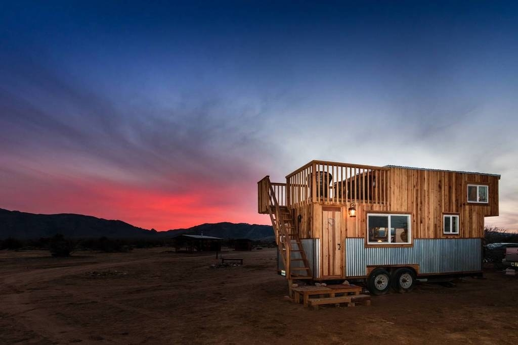 A small, wooden rectangular house on wheels, with stairs leading up to a rooftop deck. The sun is setting bright red