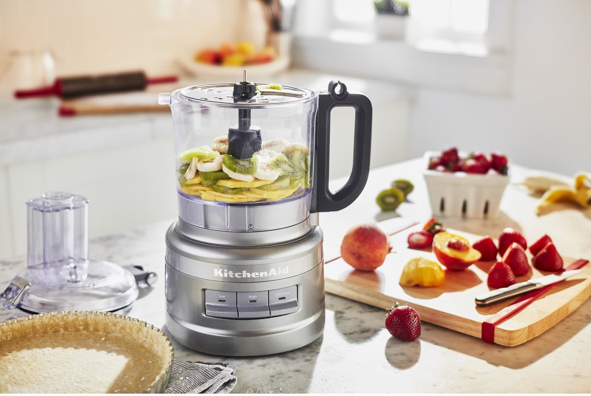 The food processor in a kitchen, full of fruit