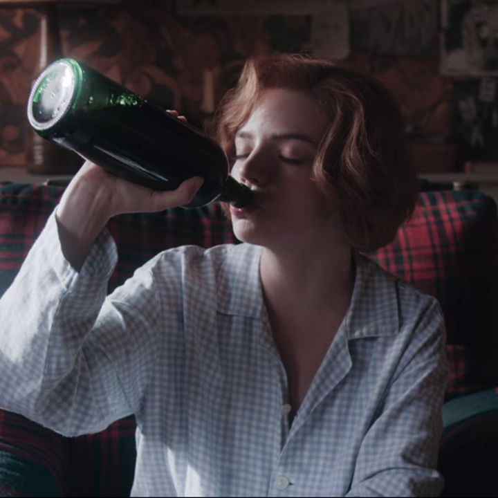 A close up of Beth drinking straight from a wine bottle; she is wearing a long-sleeved, collared shirt that is pale blue and white