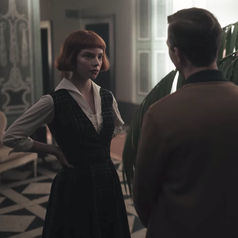 Beth standing in a room with her hands on her hips; she is talking to Matt and Mike while wearing a mid-length plaid dress with a white collared shirt underneath
