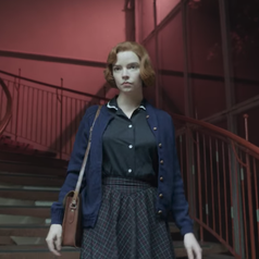 Beth walking down some stairs after her college lecture; she is wearing a navy blue blouse that has a Peter Pan collar and white piping with a dark coloured skirt, a navy blue cardigan and a brown satchel bag