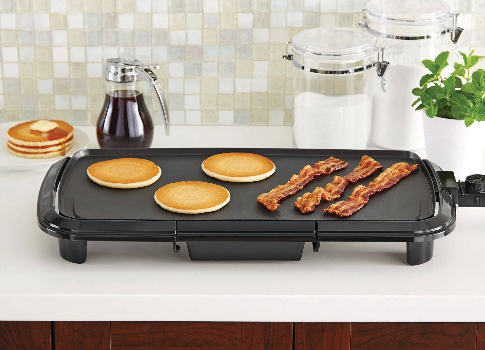 The black griddle with pancakes and bacon on a counter