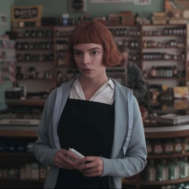 Beth in a corner shop; she is wearing a white collared top, a black pinafore and a pale blue cardigan on top