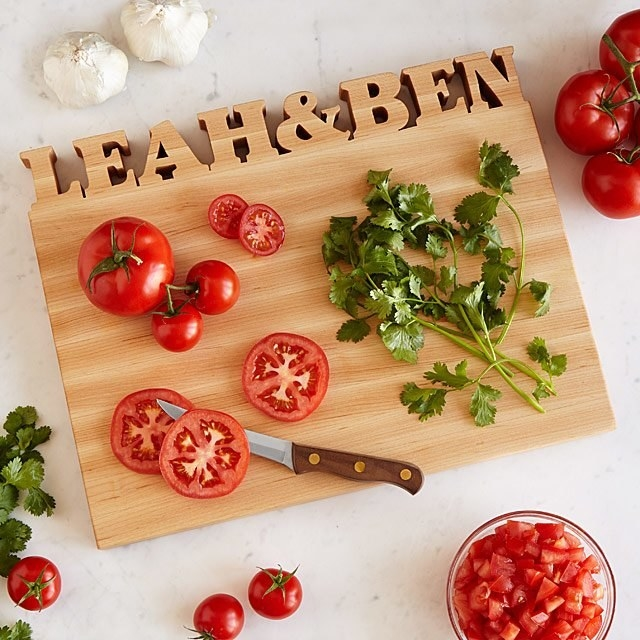 Wooden cutting board with Leah & Ben cut out at the top with tomatoes and herbs scattered on top
