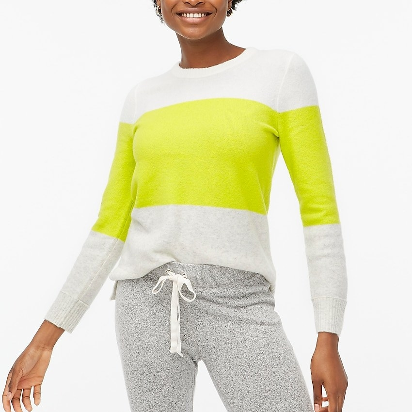 Model in the white and neon green three-stripe sweater