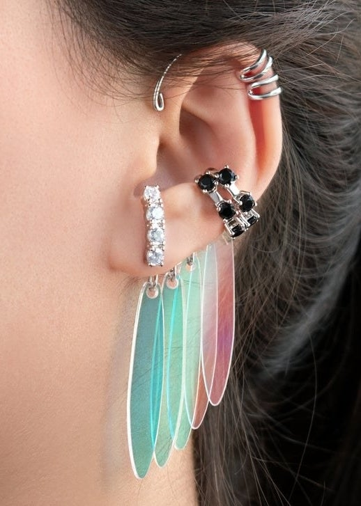 A set of three earring cuffs featuring jewels and colorful dangly parts designed like Harley Quinn's earrings from Birds of Prey