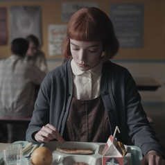 Beth sitting down and eating lunch at a school cafeteria; she is wearing a white, collared blouse, a brown pinafore and a teal-coloured cardigan
