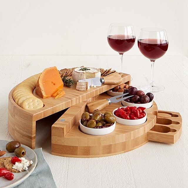 Cheese plate opened up to reveal swivel compartment with various snacks and toppings, and the hidden drawer opened to reveal cheese knives