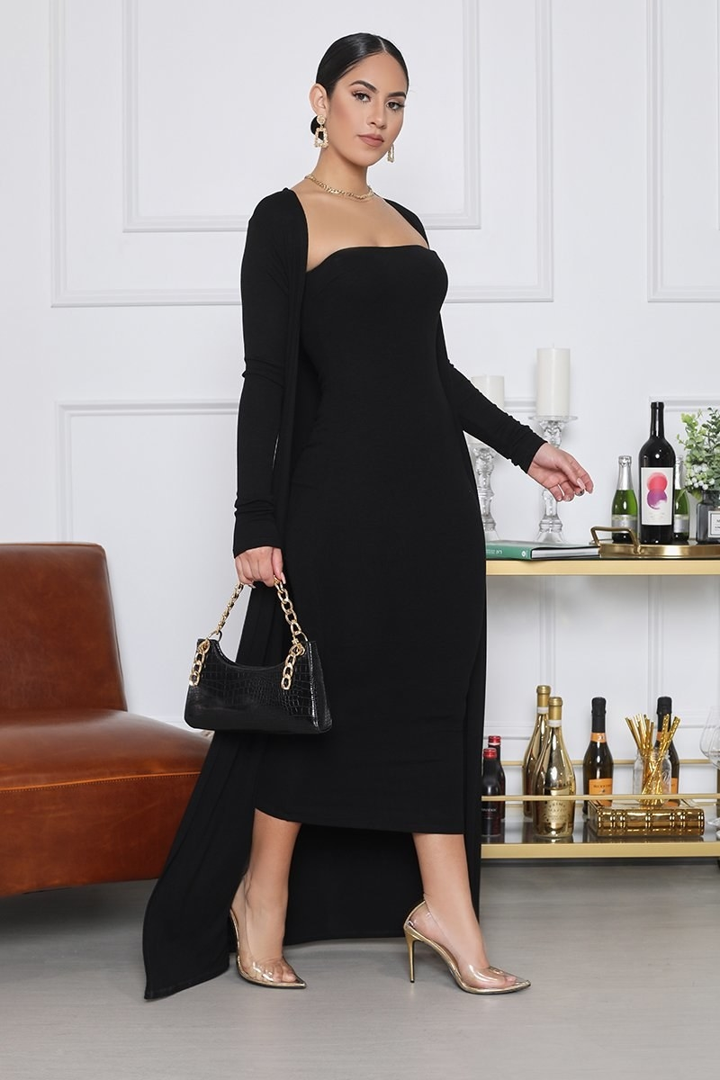A model in the black dress and cardigan