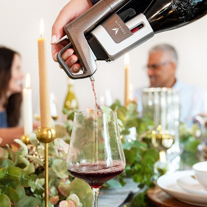 Model pouring glass of red wine into glass using wine preserver.