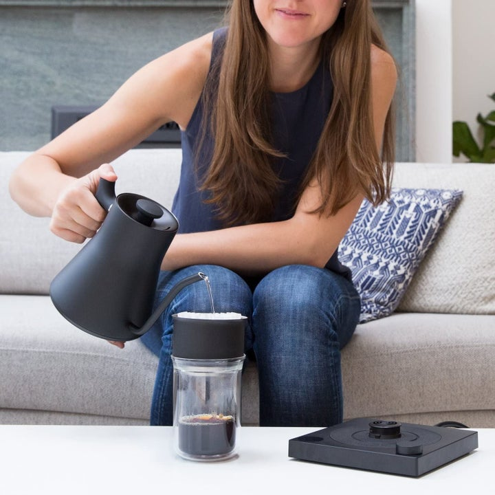 Model pouring water from kettle into coffee tumbler