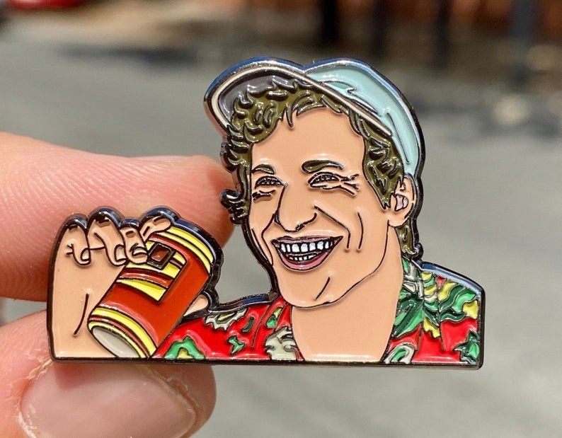 A label pin of Andy Samberg in his costume from the movie Palm Springs, smiling and holding a beer can