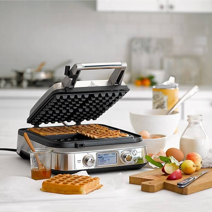 Waffles cooking in opened waffle maker placed on kitchen counter