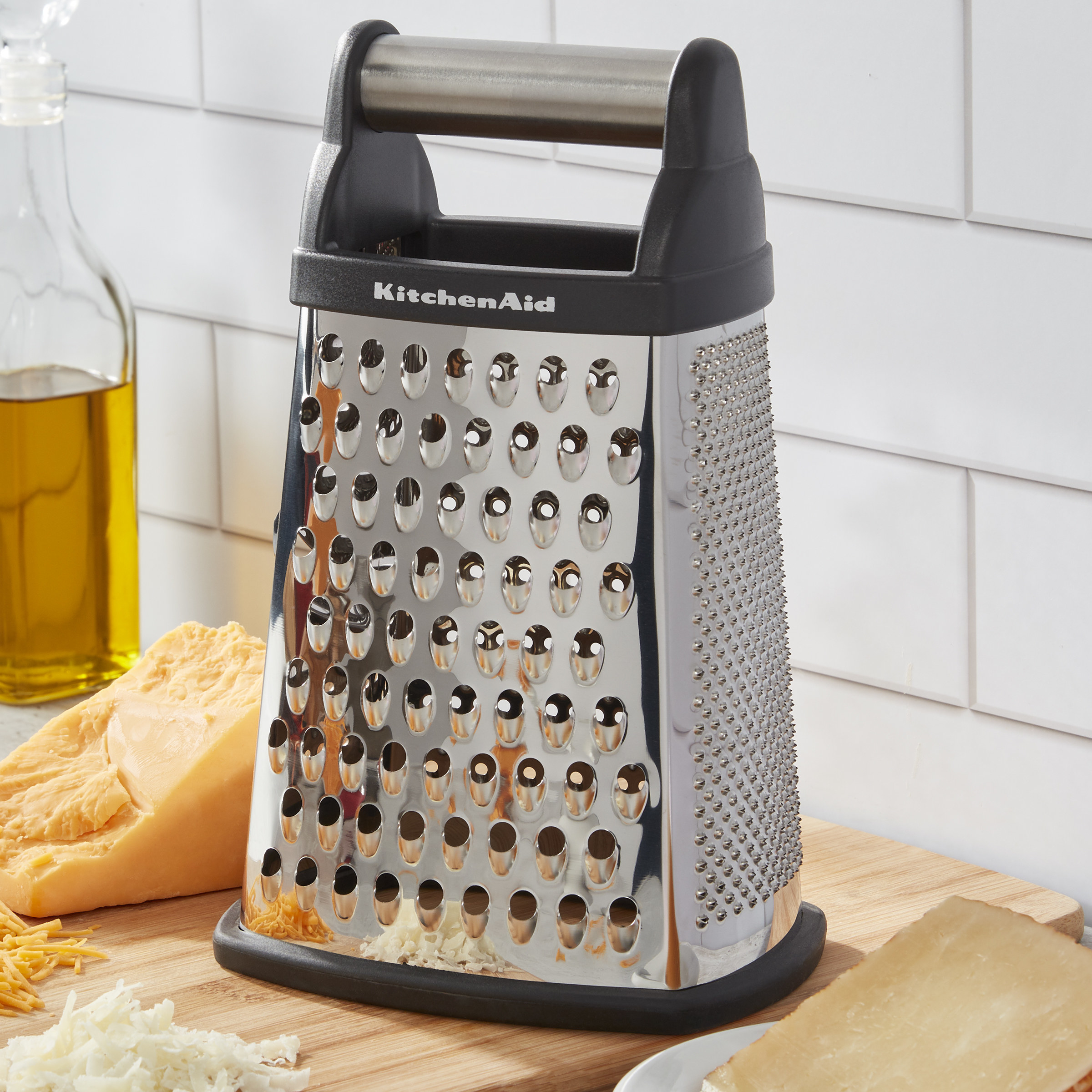 The silver-colored KitchenAid box greater, pictured on a cutting board with cheeses
