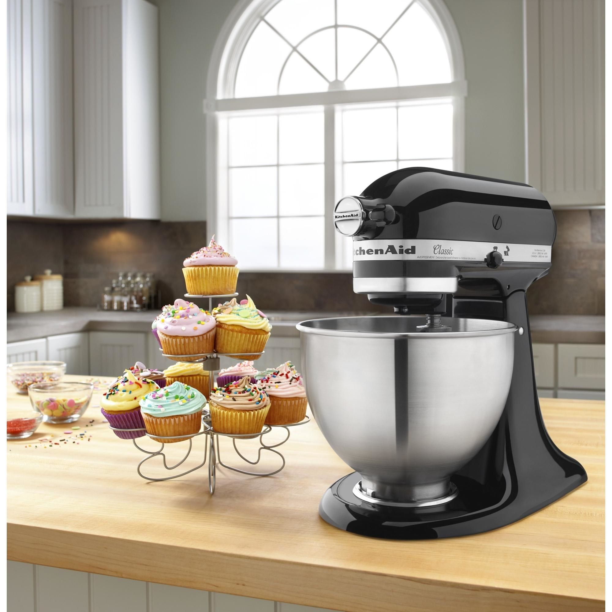 The black KitchenAid mixer, pictured in a kitchen with cupcakes