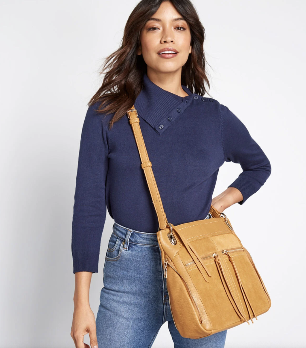 Model with a yellow cross body messenger bag with tasseled zippered front pockets