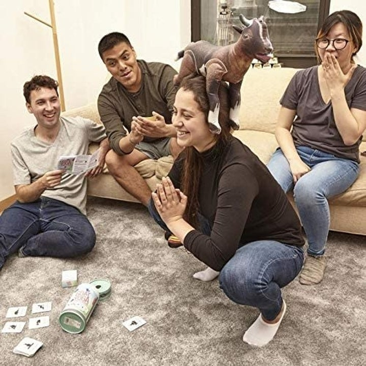 More models playing the game, with cards on the floor and a player with the goat on their head