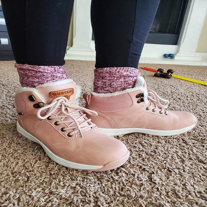 a reviewer wearing the lace-up ankle hiking boots in pink