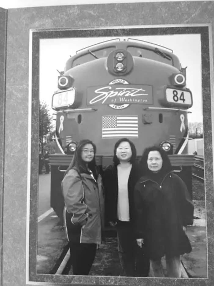 The Lee family poses in front of a train