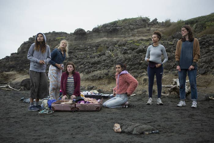 Six teen girls stand and kneel on a beach on an overcast day, a suitcase of clothes open before them