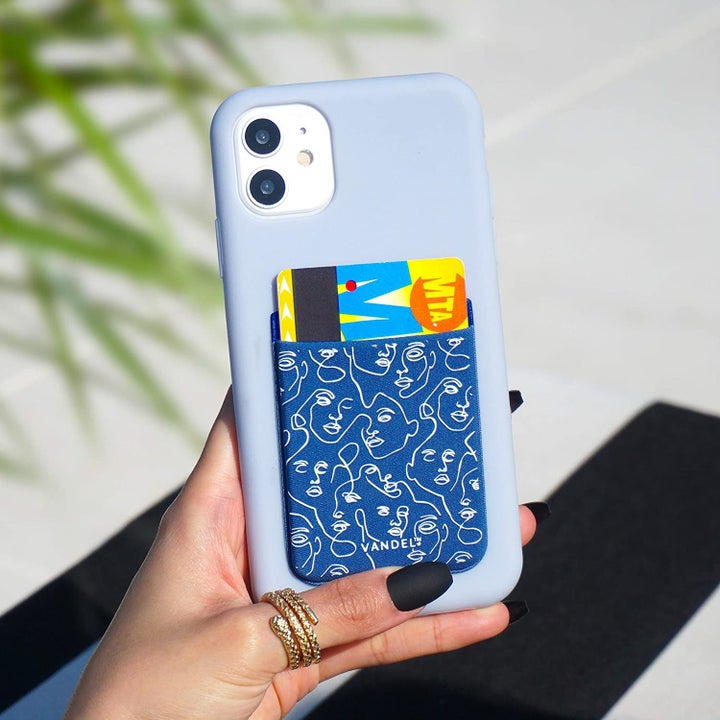 A hand holding a phone with the blue and white face print pocket attached to the case, holding a Metro card
