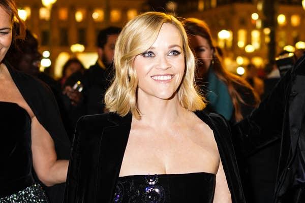 Reese Witherspoon mengenakan gaun off-shoulder dan jaket beludru hitam, di luar Armani, selama Paris Fashion Week - Haute Couture Musim Semi / Musim Panas 2020, pada 21 Januari 2020 di Paris, Prancis
