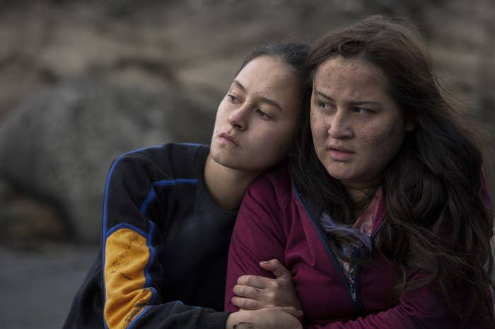 Two teen girls, each with dirty faces and wind in their hair, hold each other outside in the cold