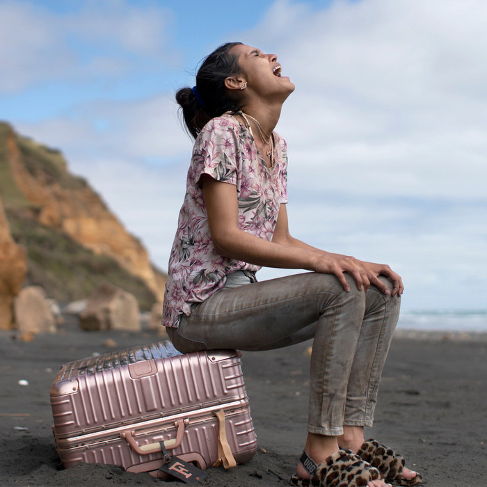 A teen girl sits on a suitcase on the beach and cries