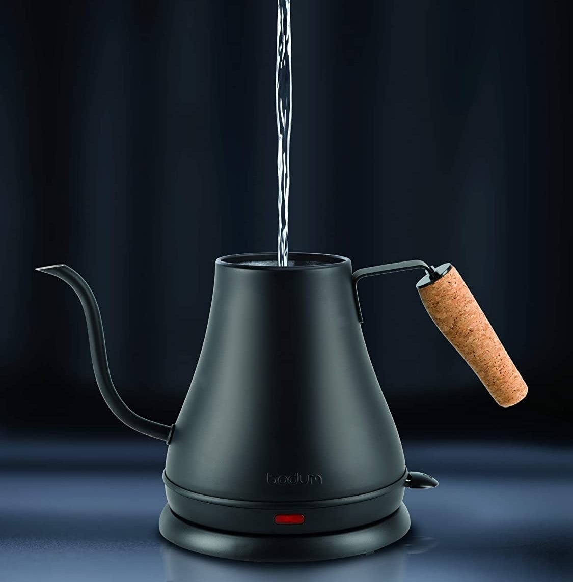 A person pouring water into the kettle
