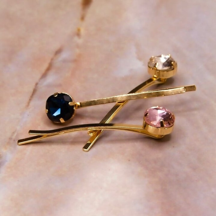 Three gold pins each with a large jewel on one end in clear, navy, and pink