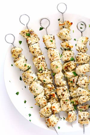 Several chicken skewers on a plate.