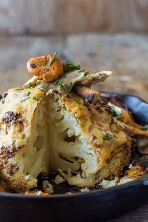 A whole roasted cauliflower with a slice taken out of it.