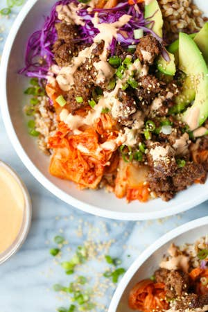 A close-up of a Korean beef bowl with cabbage, carrots, and avocado.
