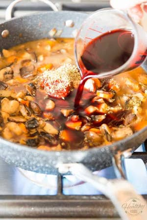 Pouring red wine into a skillet with mushrooms and onion.