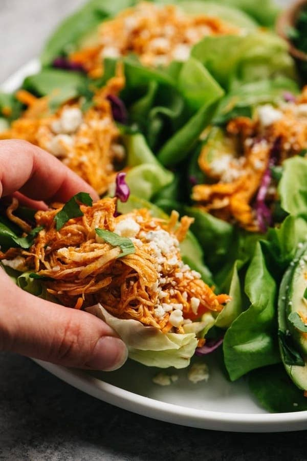A hand holding a lettuce wrap stuffed with buffalo chicken.