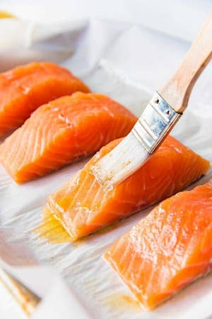 Brushing salmon fillets with a butter mixture.