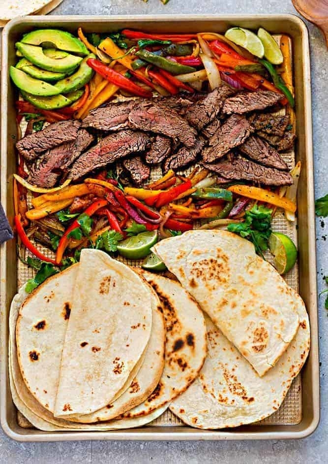 A sheet pan with roasted veggies, sliced steak, and tortillas.