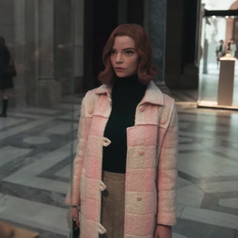 Beth staring at something in the distance; she is wearing a black turtleneck, a marle grey skirt and a pink and white coat on top