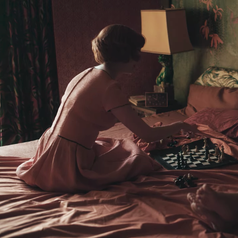 Beth sitting on a hotel bed with her mother while playing a chess game; she is wearing a short-sleeved, peach-coloured dress