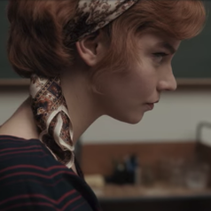 A closeup of Beth's side profile; she is wearing a patterned scarf in her hair and a red and navy blue striped blouse