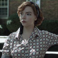 Beth sitting on a bench outdoors; she is wearing a short-sleeved, collared red and blue patterned shirt and a headscarf